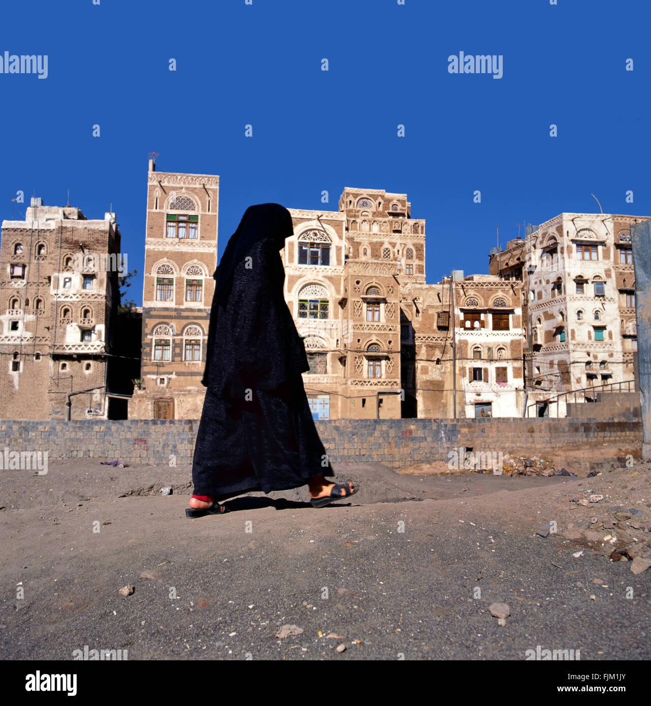 A veiled Muslim woman walks on a Sana a street, Yemen.At background typical Yemen houses. - Stock Image