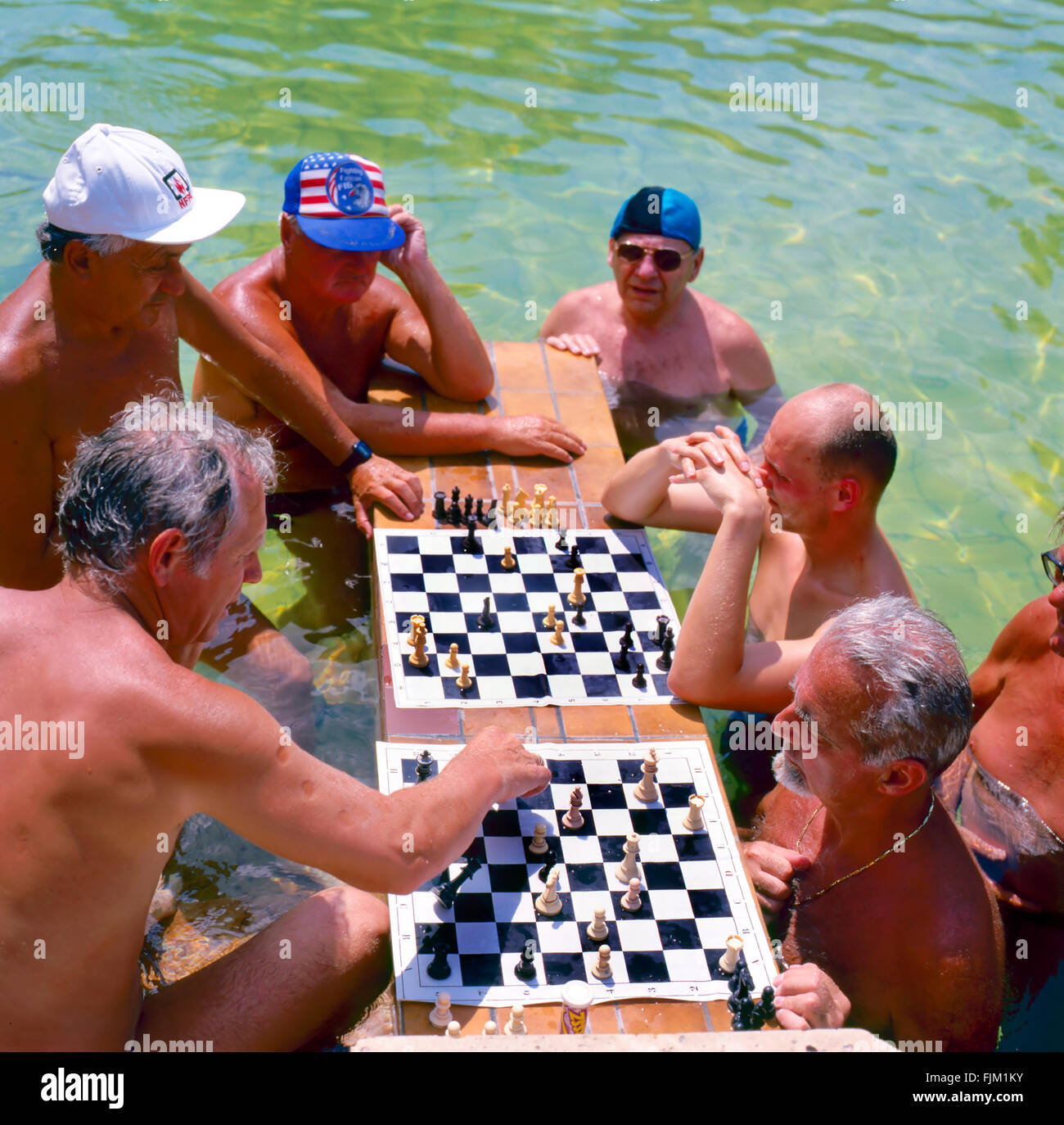 Men playing chess in the Szechenyi thermal baths, spa and swimming pool in Budapest Hungary Focused at the first Stock Photo