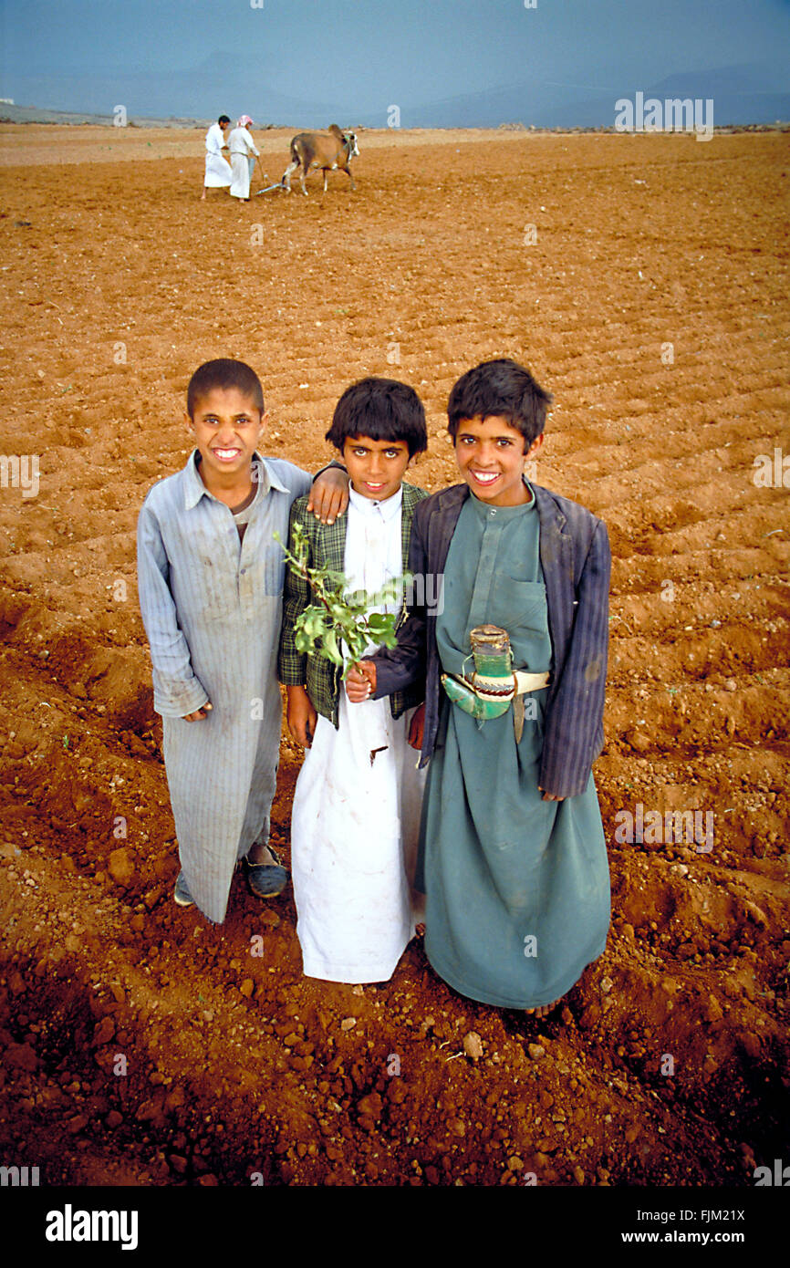 Three friends posing in their djellabas at the fields of the farm of their parents.At the background their fathers - Stock Image