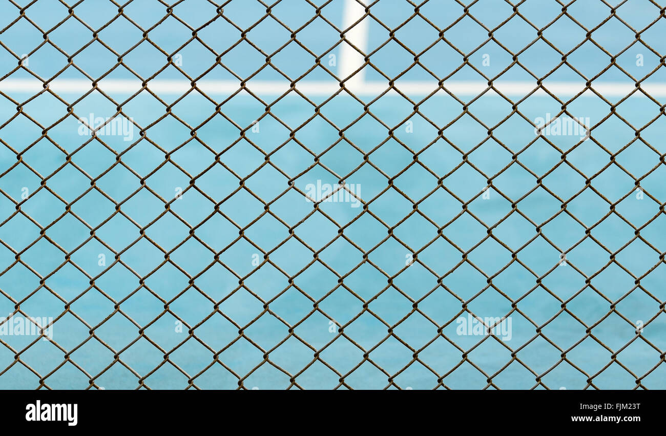 Metal Mesh fence on blurred background of blue tennis hard court ...