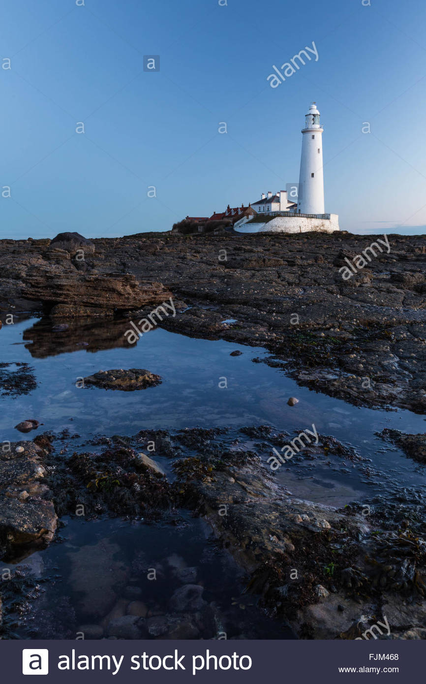 Lighthouse with a rock pool in the foreground. - Stock Image