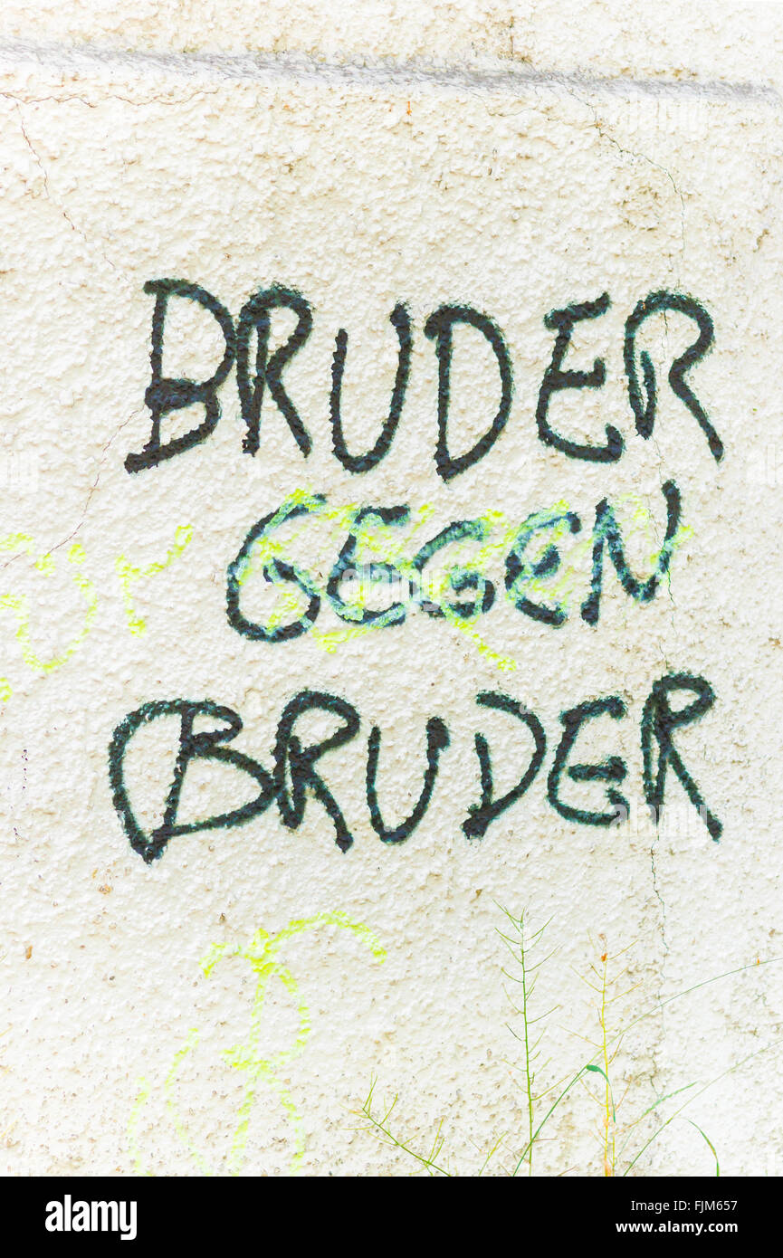 graffito on a wall with a text that reads: brother against brother Stock Photo