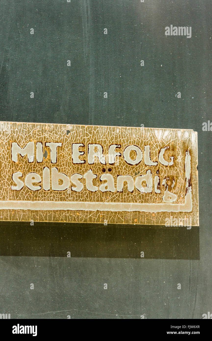 faded sticker on a wall bearing the inscription: successfully self-employed - Stock Image