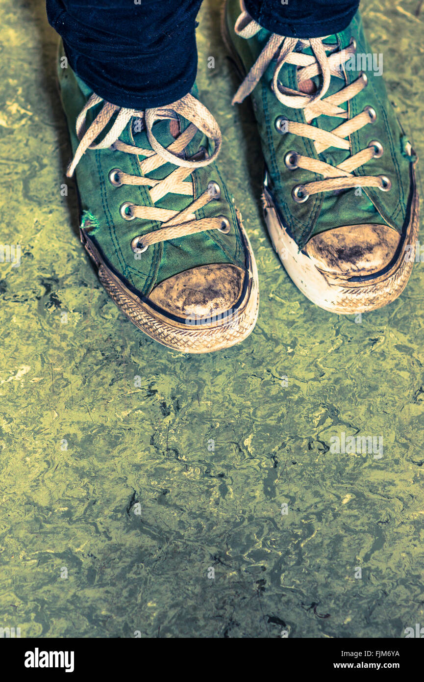 green sneakers against greenish  floor - Stock Image