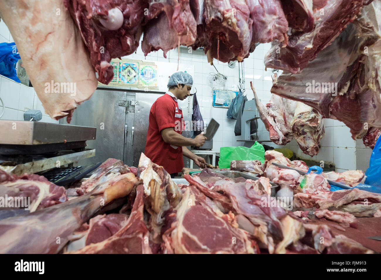 Butcher working in Dubai meat market in Deira United Arab Emirates - Stock Image