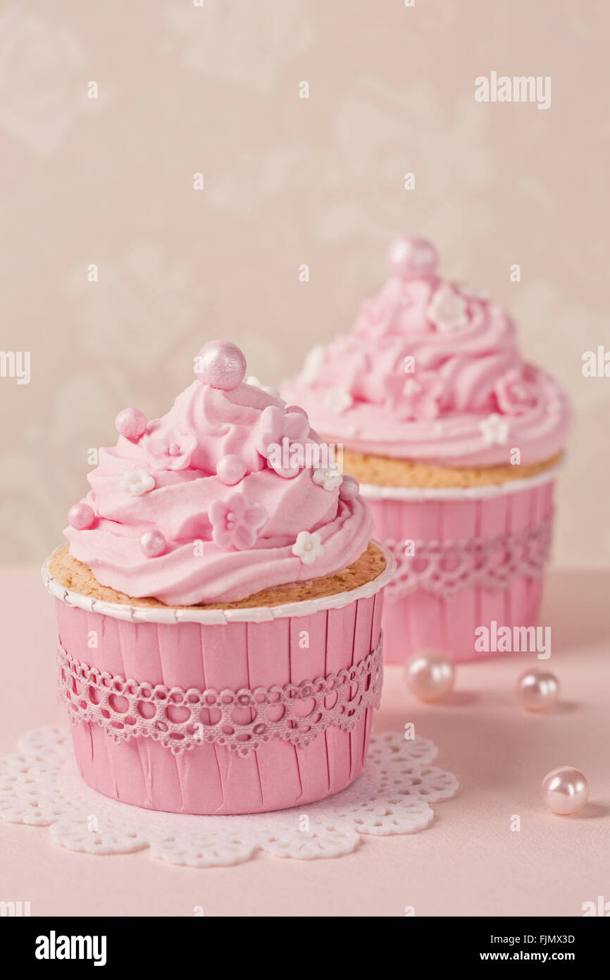 Pink cupcakes on a beige background - Stock Image