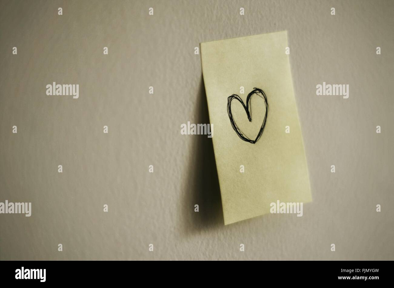 Close-up Of Adhesive Note With Heart Shape Stuck On Wall - Stock Image
