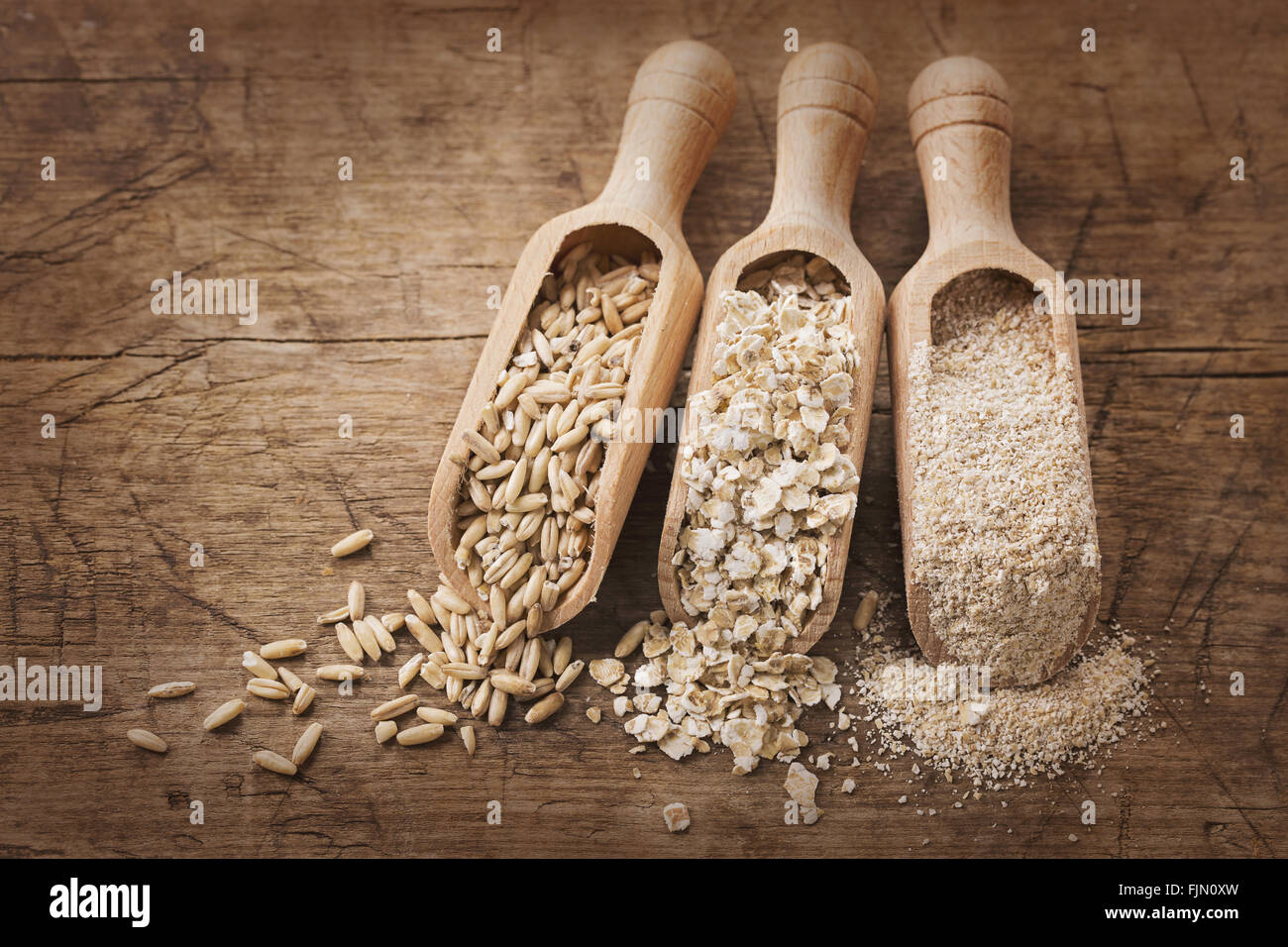 Oat flakes, seeds and bran in spoons - Stock Image