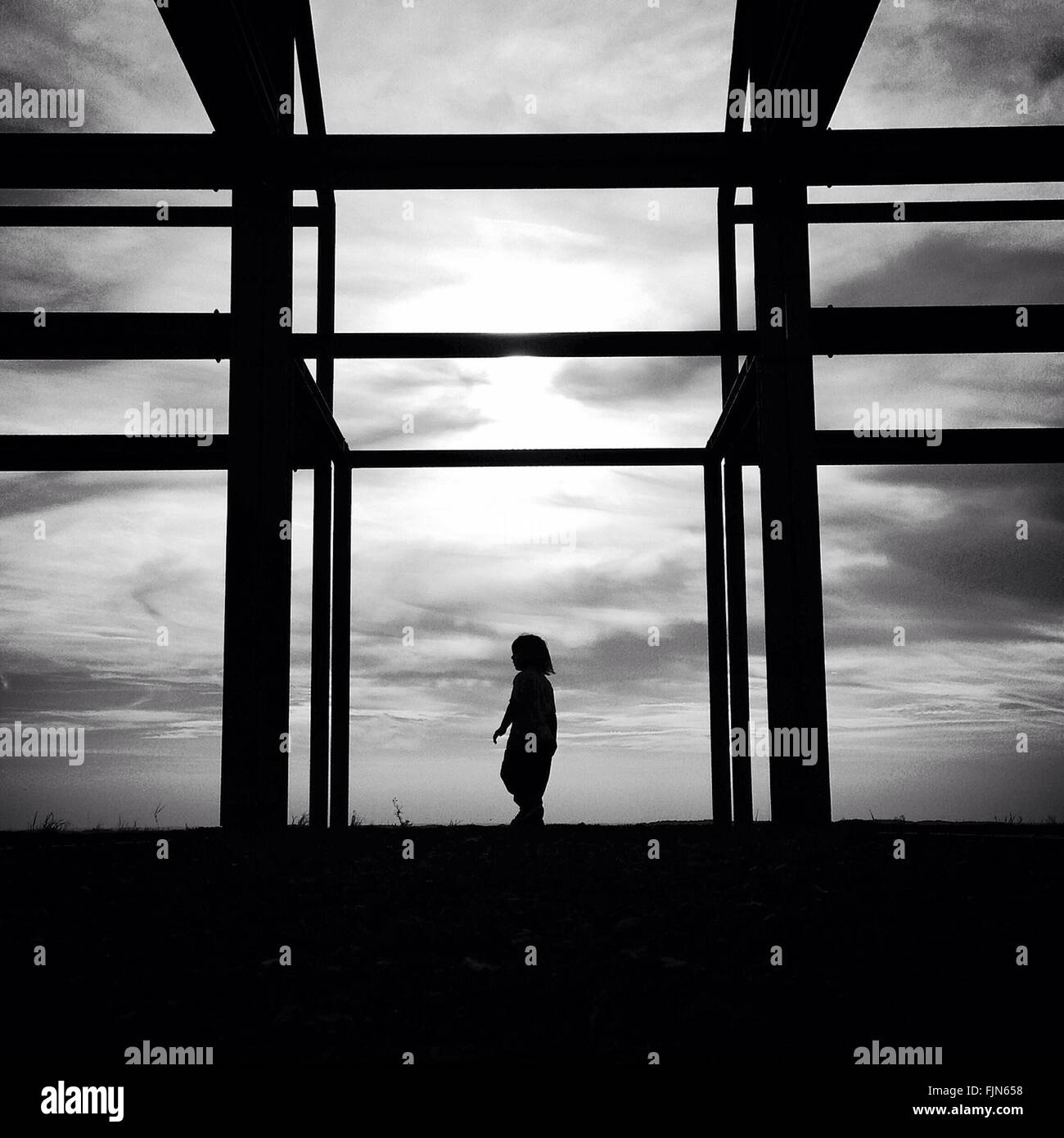 Silhouette Girl Standing At Low German Hallhouse Framework Against Sky - Stock Image