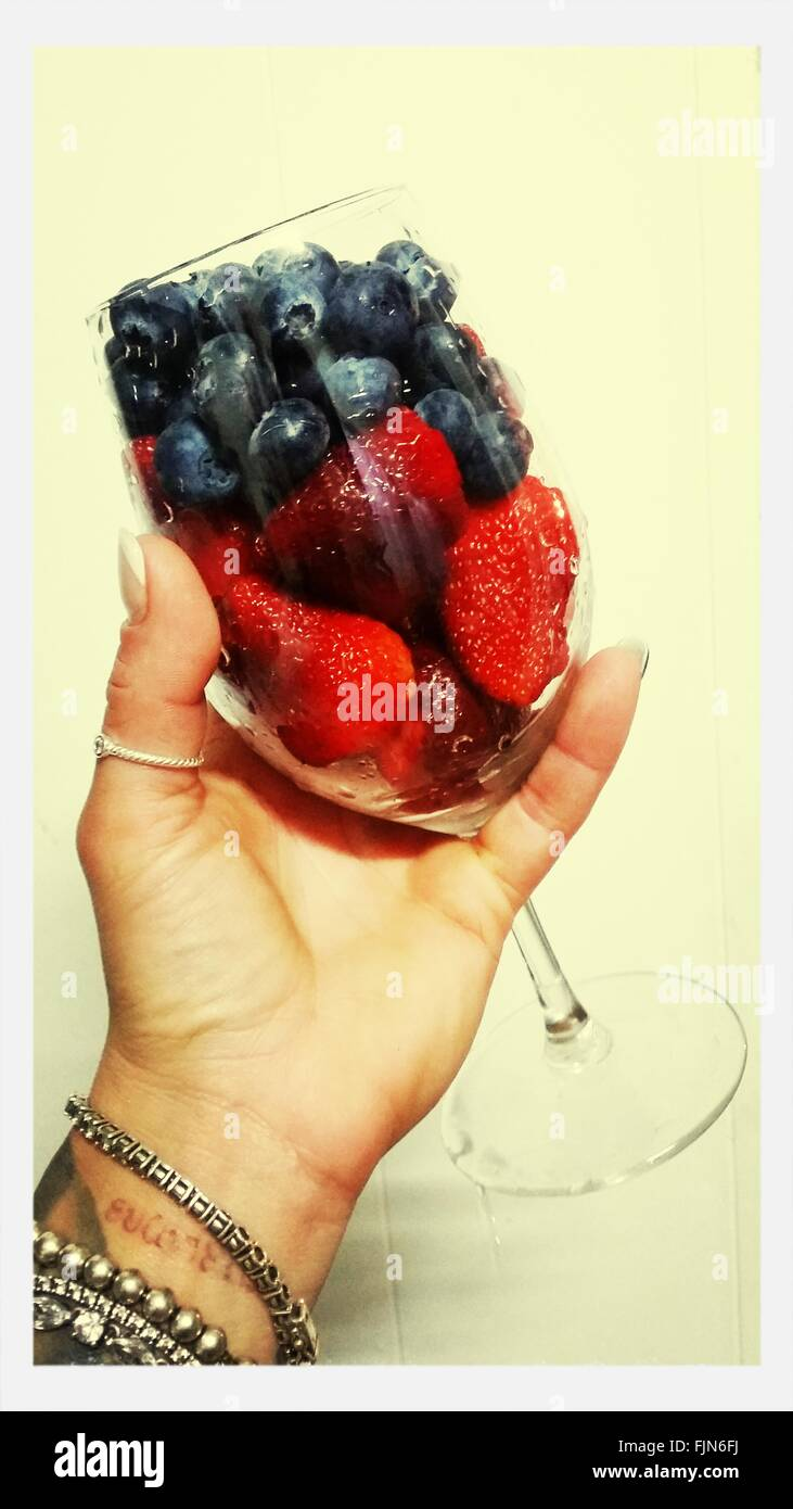 Cropped Image Of Hand Holding Fruits In Wineglass Against Wall - Stock Image