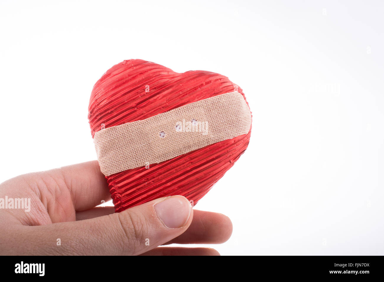 Hand Holding A Hurt Heart With Plaster In Hand On White Background