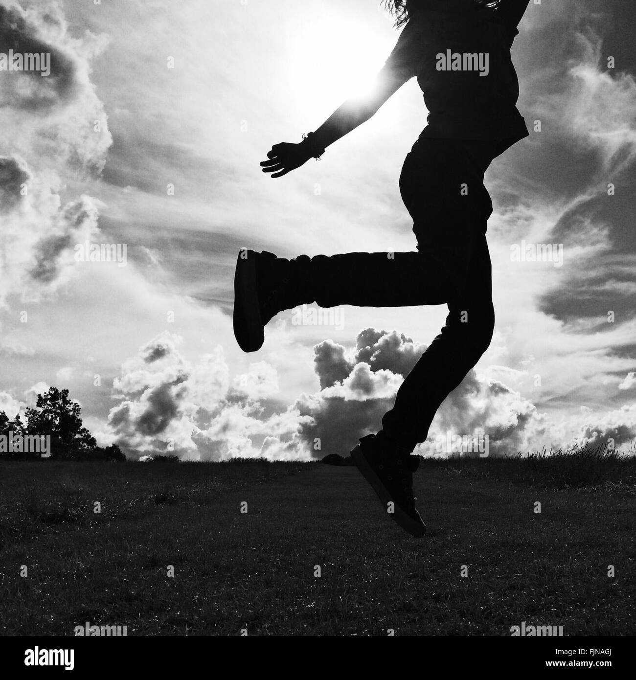 Silhouette Low Section Of Girl Jumping On Landscape Against Sky - Stock Image