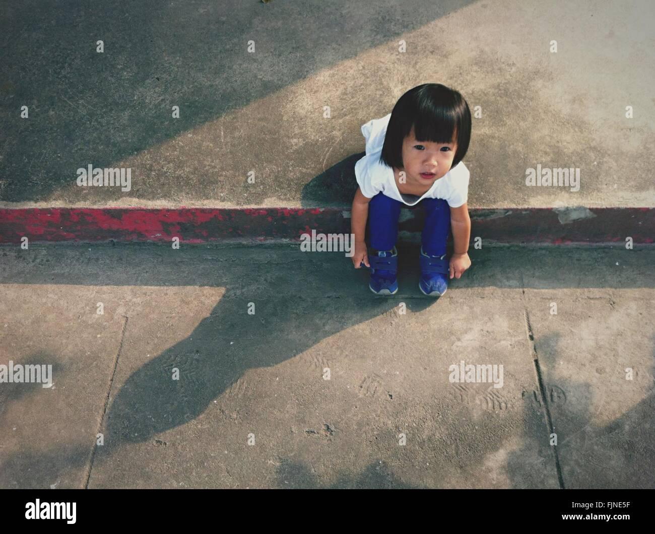 High Angle View Of Girl Sitting On Sidewalk - Stock Image