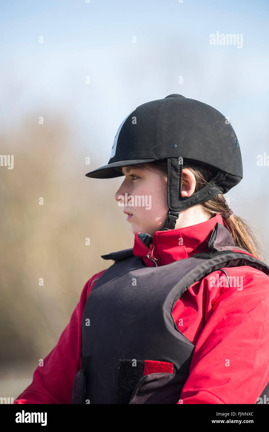 Upper body of a girl with red jacket, black protective gear vest and helmet at a riding lesson - Stock Image