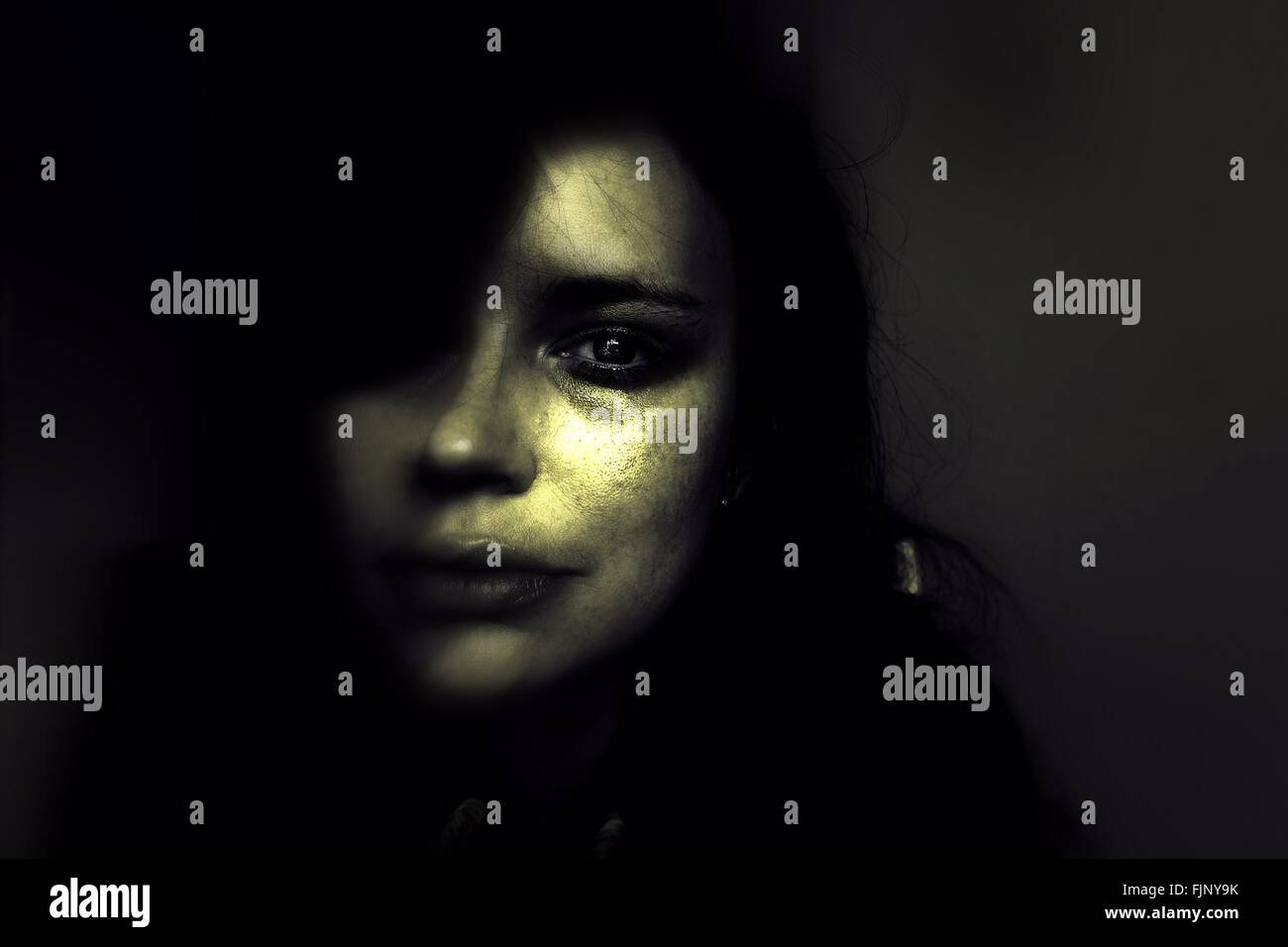 Close-Up Portrait Of Sad Woman In Darkroom - Stock Image