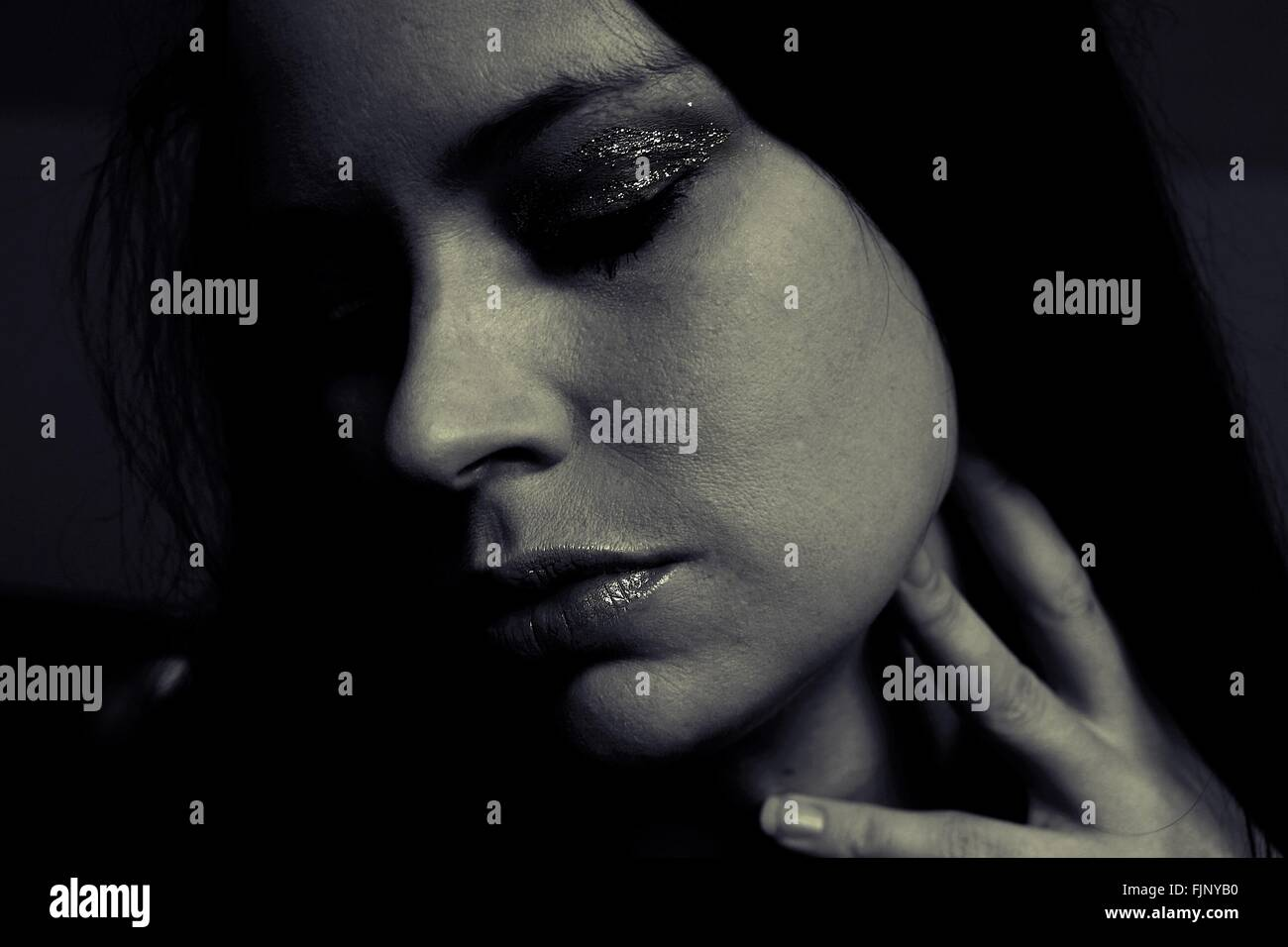 Close-Up Of Thoughtful Young Woman Against Black Background - Stock Image