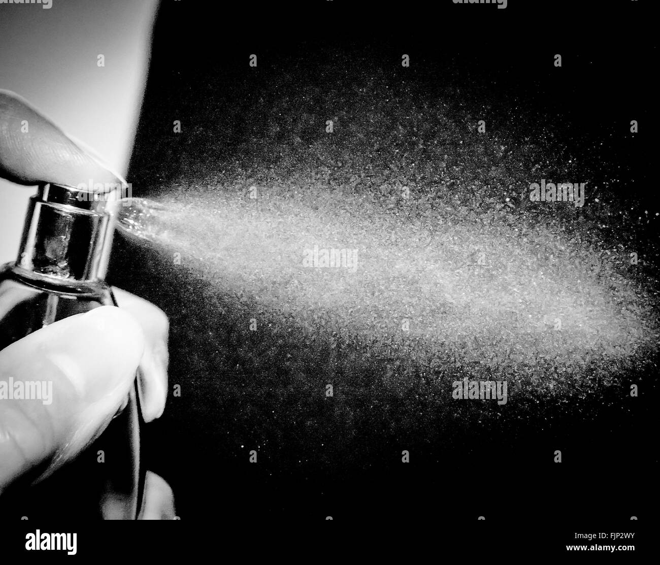 Cropped Woman Hand Spraying Perfume - Stock Image