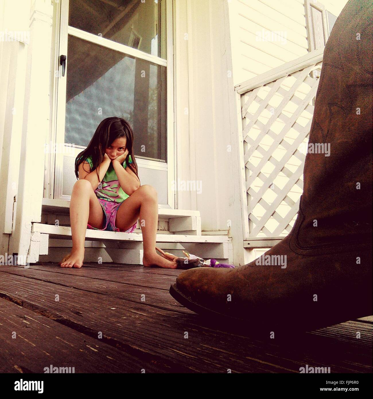 Low Angle View Of Girl Sitting On Steps - Stock Image