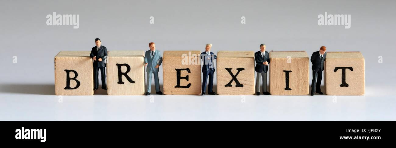Wooden blocks spelling the word Brexit with a miniature business men in suits standing between the letters - Stock Image