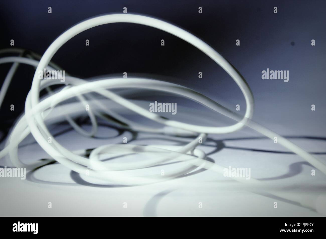 Close-Up Of Wires Against Plain Background - Stock Image