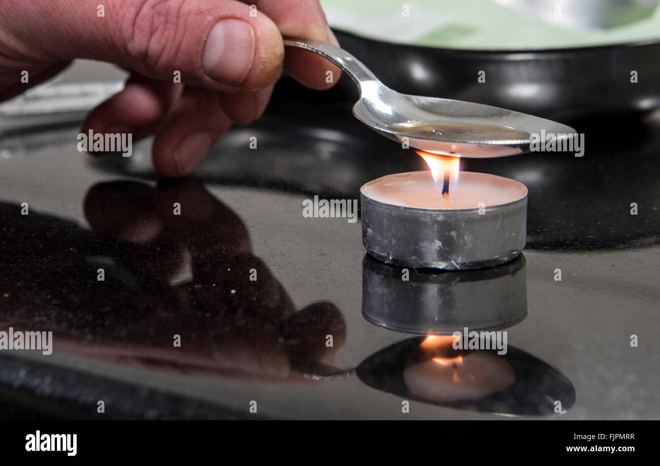 37-year-old drug addict Marc (name altered upon request) heats a shot of heroin using a spoon at a supervised injection - Stock Image