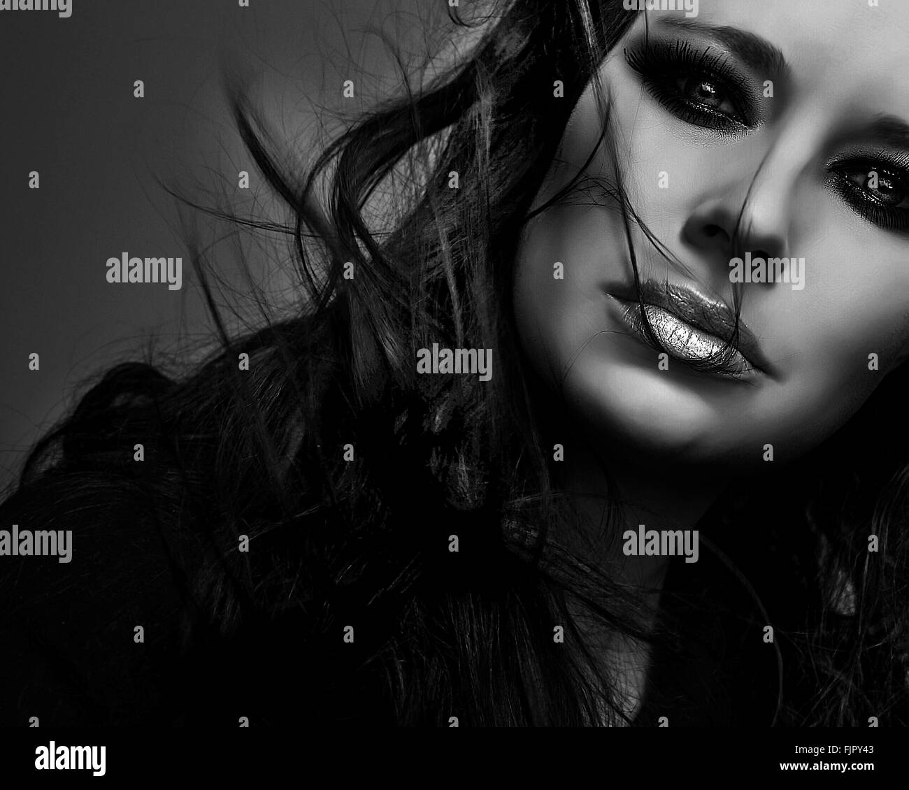 Close-Up Portrait Of Beautiful Woman With Make-Up Against Gray Background - Stock Image