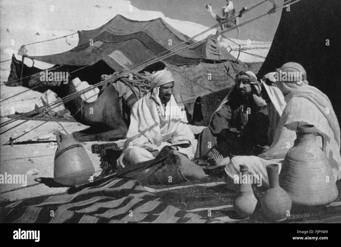 Bedouin in 1930s in the Holy Land  with their tents and camels. - Stock Image