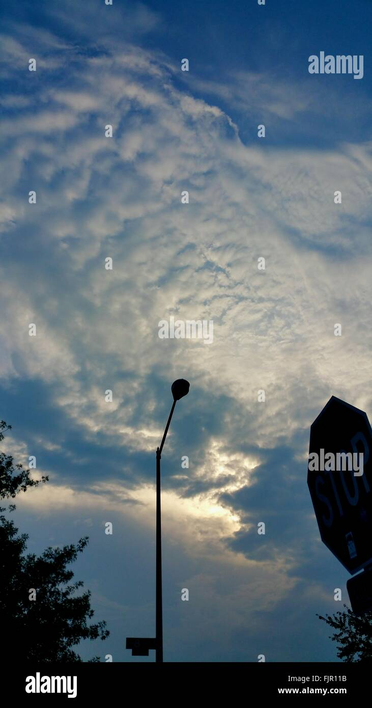 Low Angle View Of Road Sign And Street Light Against Cloudy Sky Stock Photo