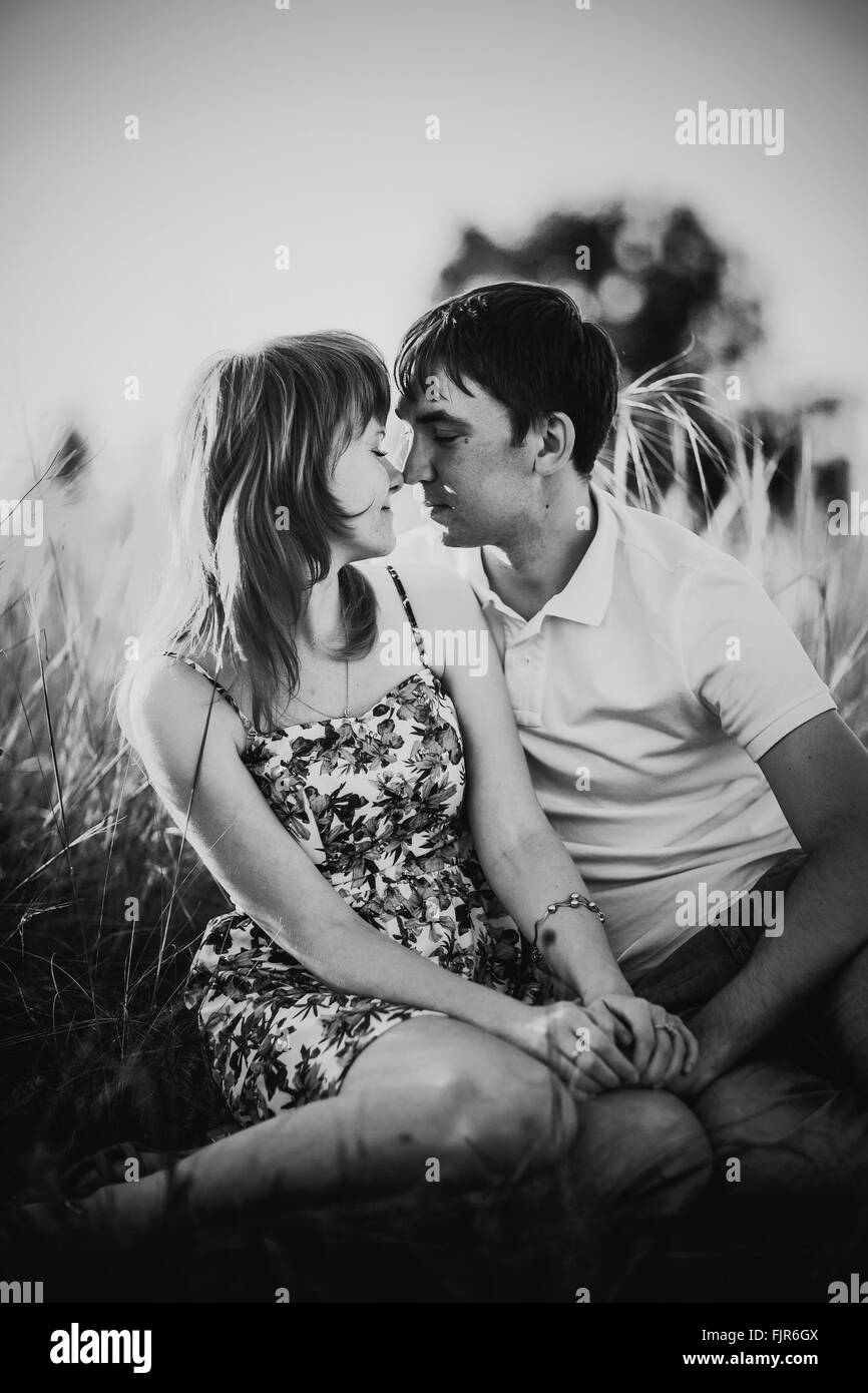 Black white photography romantic couple standing and kissing on background summer meadow sunset