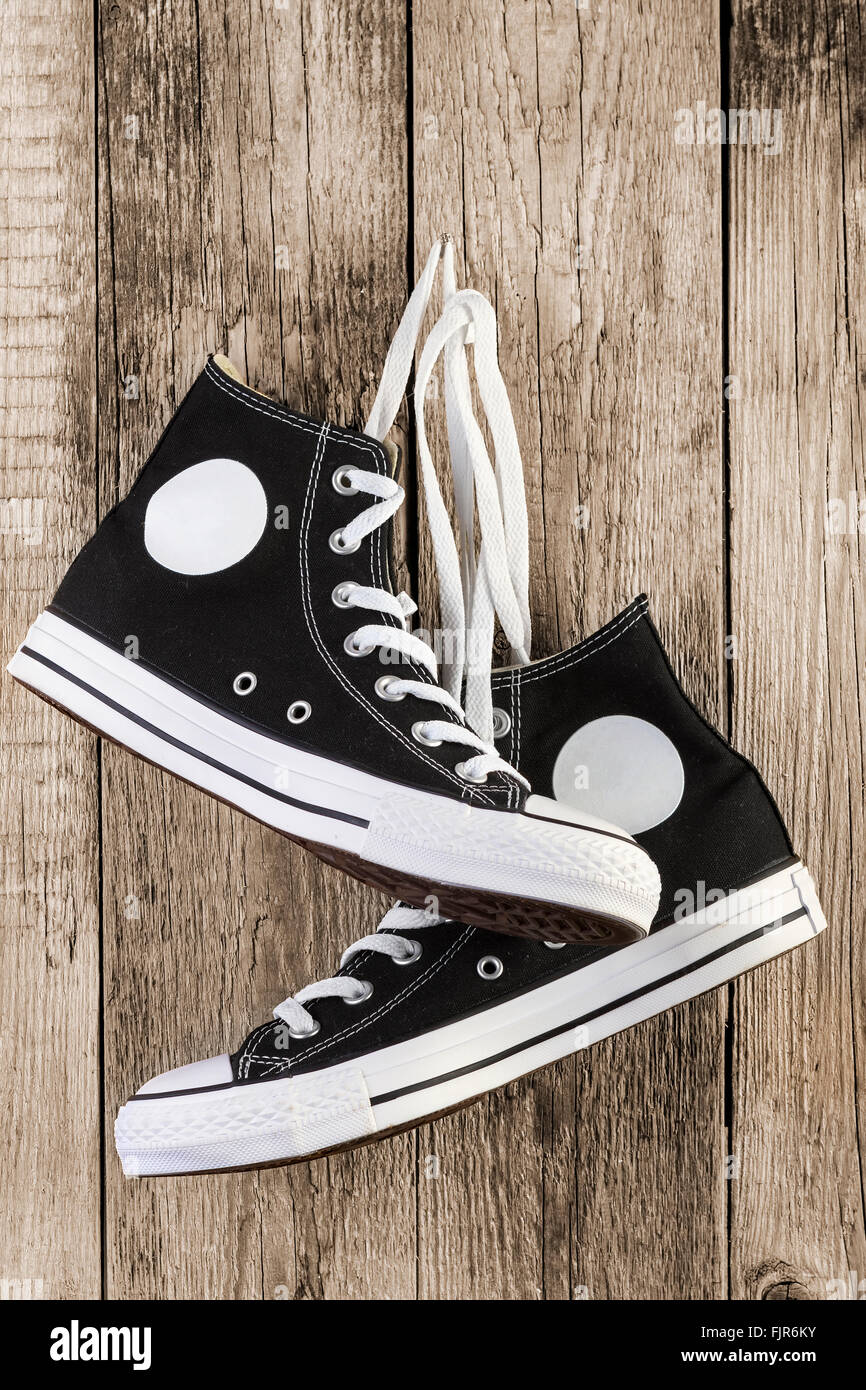 Black sneakers shoes on wooden background. - Stock Image