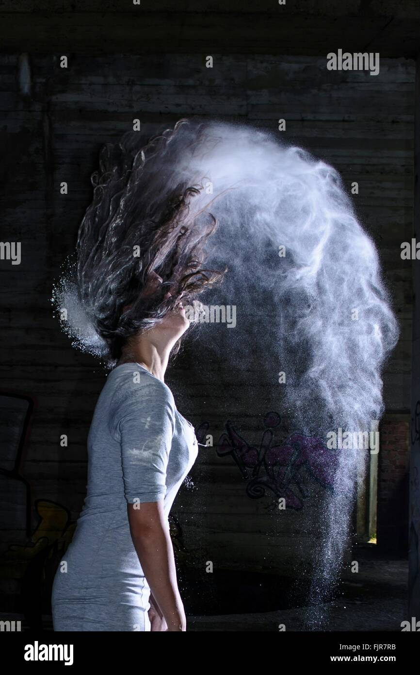Side View Of Woman Flipping Hair In Powder - Stock Image