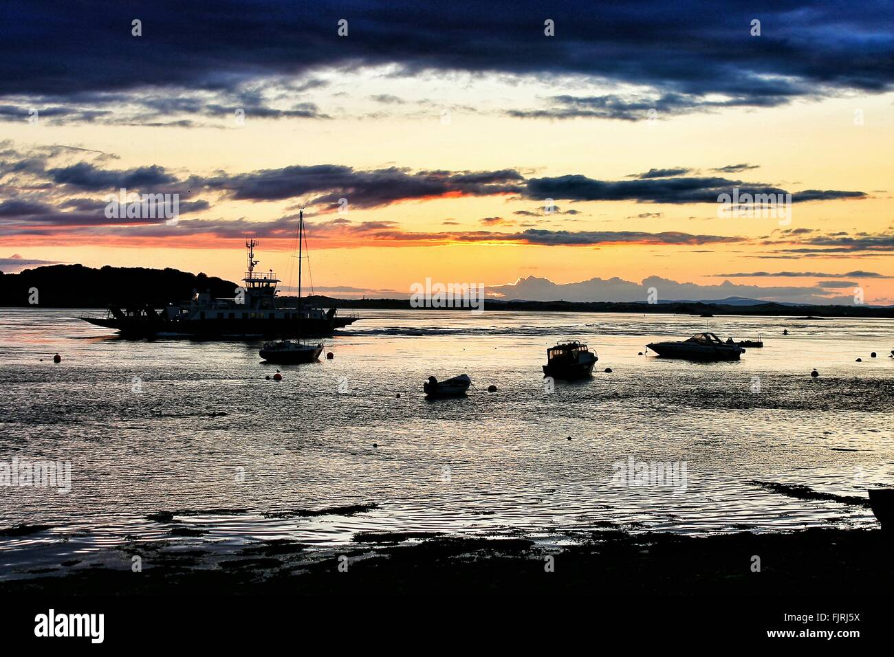 Silhouette Boats Anchored In Sea Against Sunset Sky - Stock Image