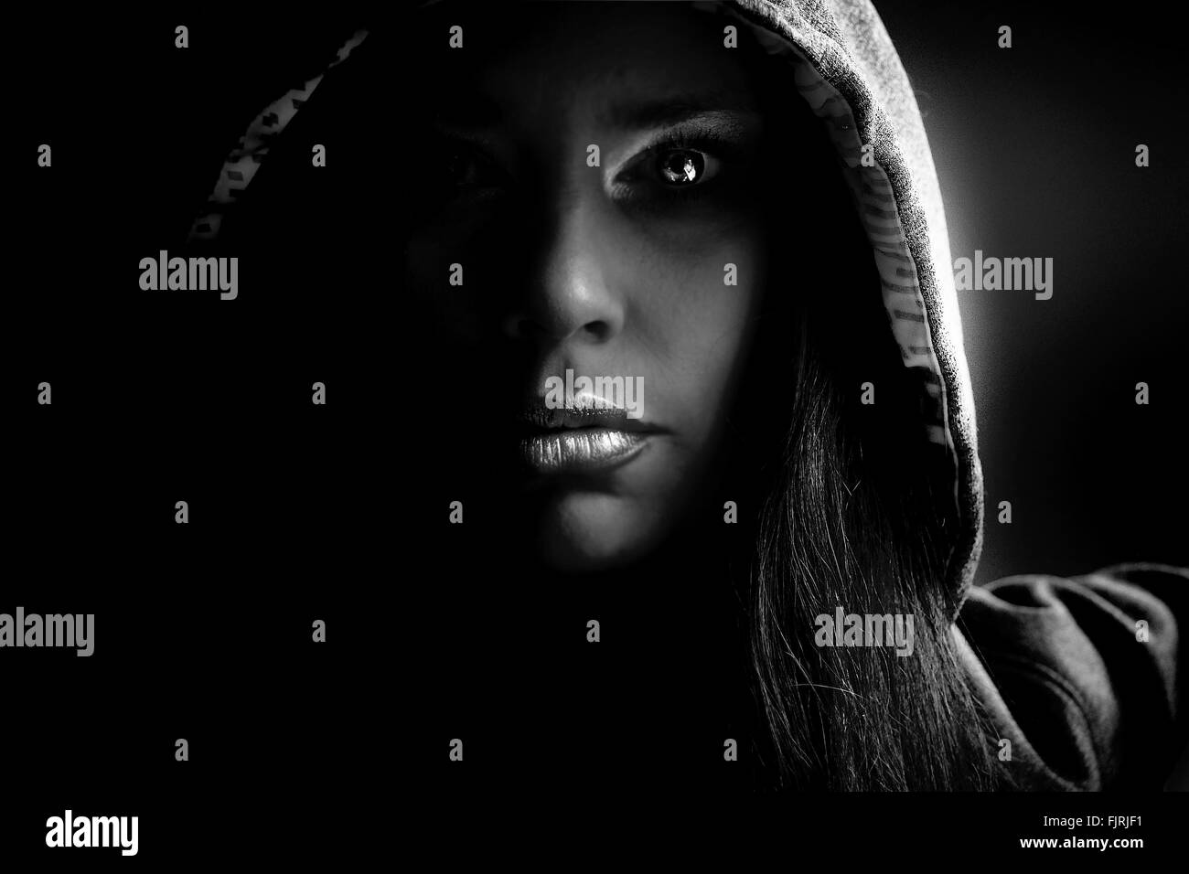 Close-Up Of Young Woman Wearing Hooded Shirt At Home - Stock Image