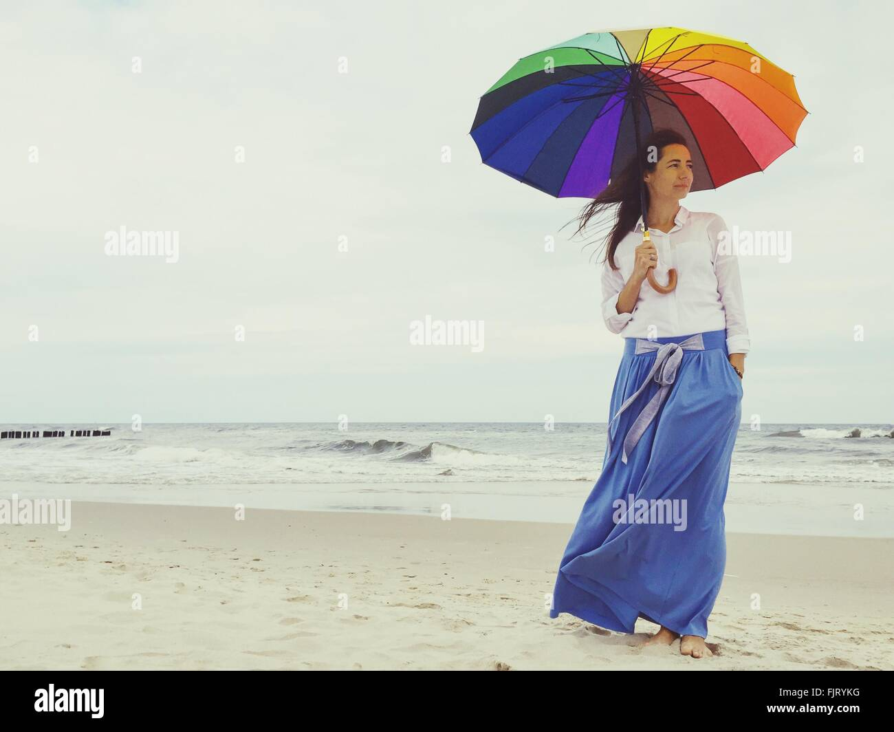 Young Woman Standing With Umbrella On Beach Against Sky Stock Photo
