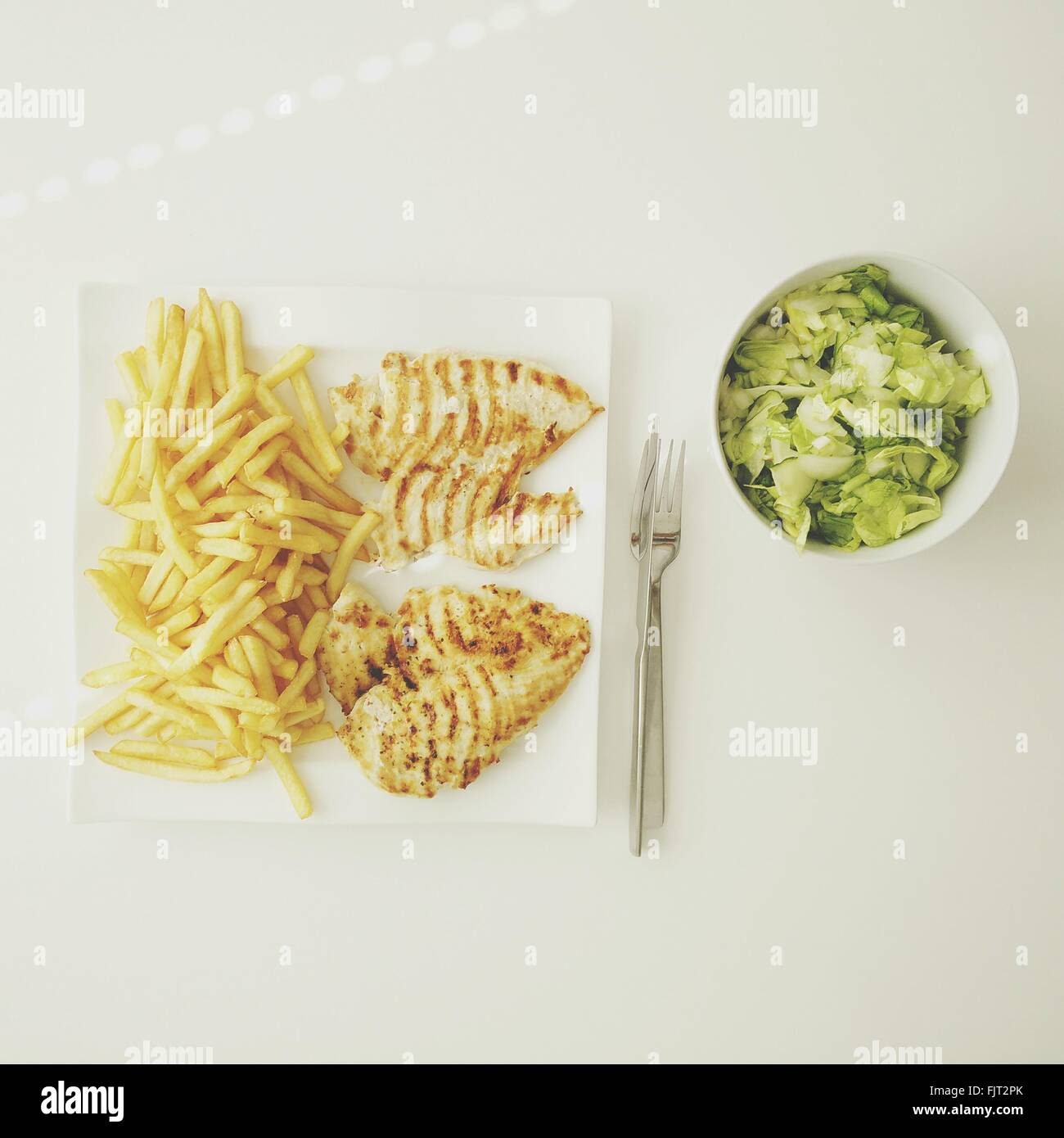 Directly Above View Of French Fries And Meat With Lettuce Against White Background - Stock Image