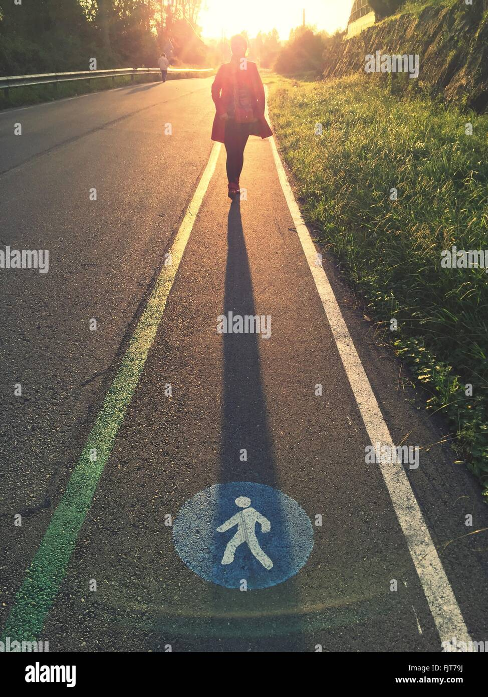 Person Walking On Illuminated Street - Stock Image