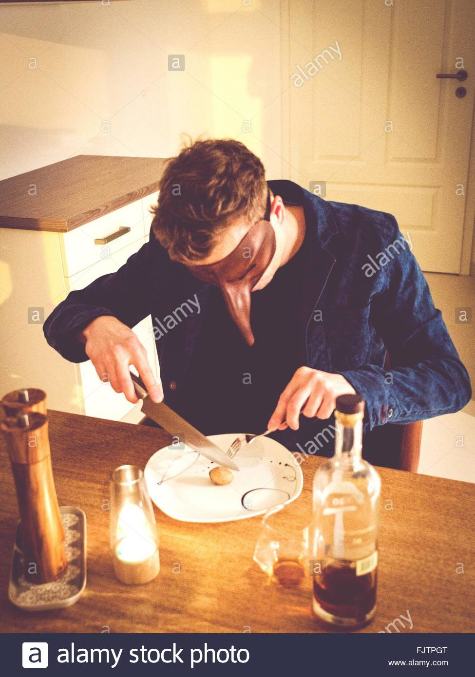 Man With Mask Eating Breakfast At Home Stock Photo