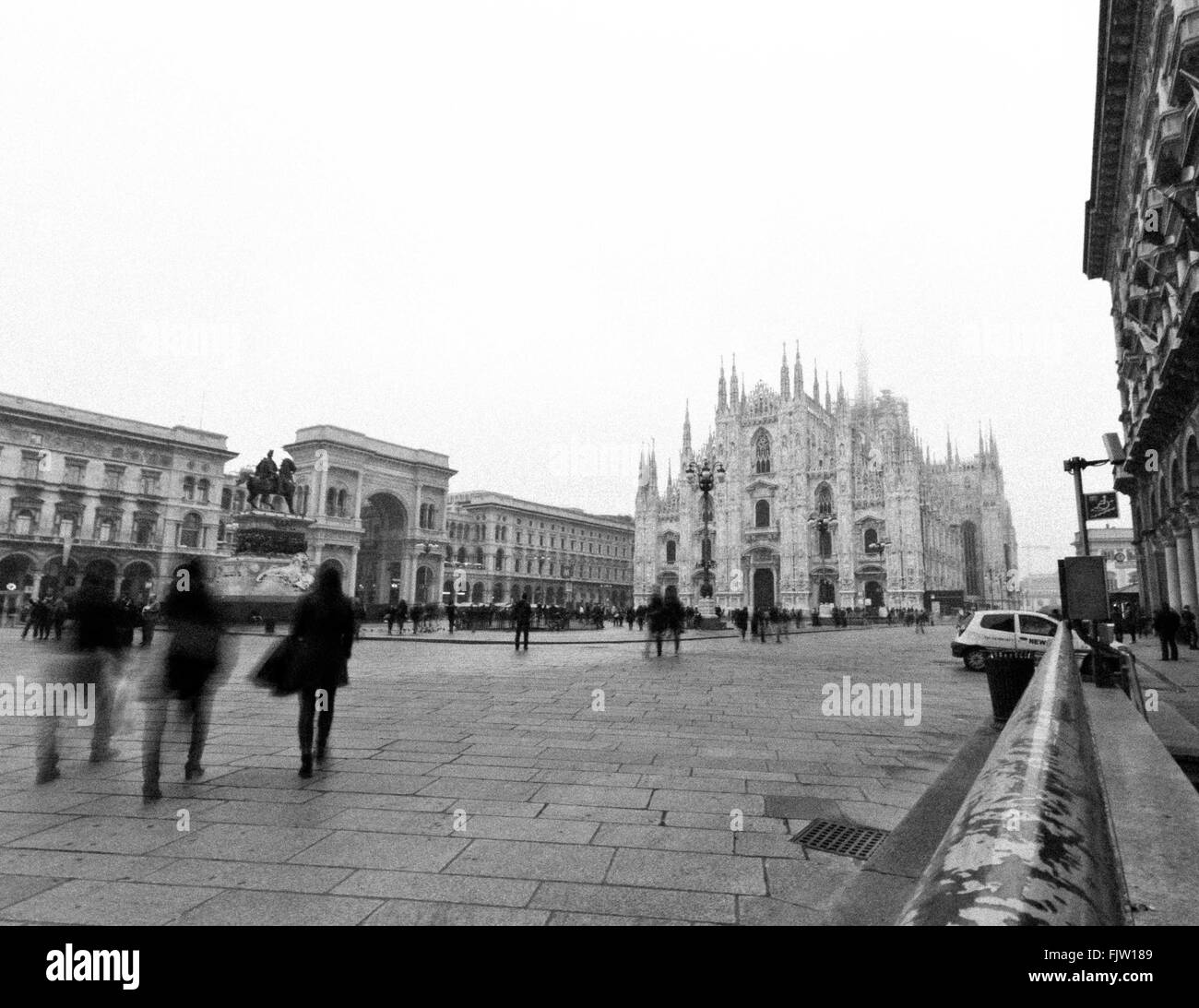 Blurred Motion On People Walking On Street Against Duomo Di Milano - Stock Image