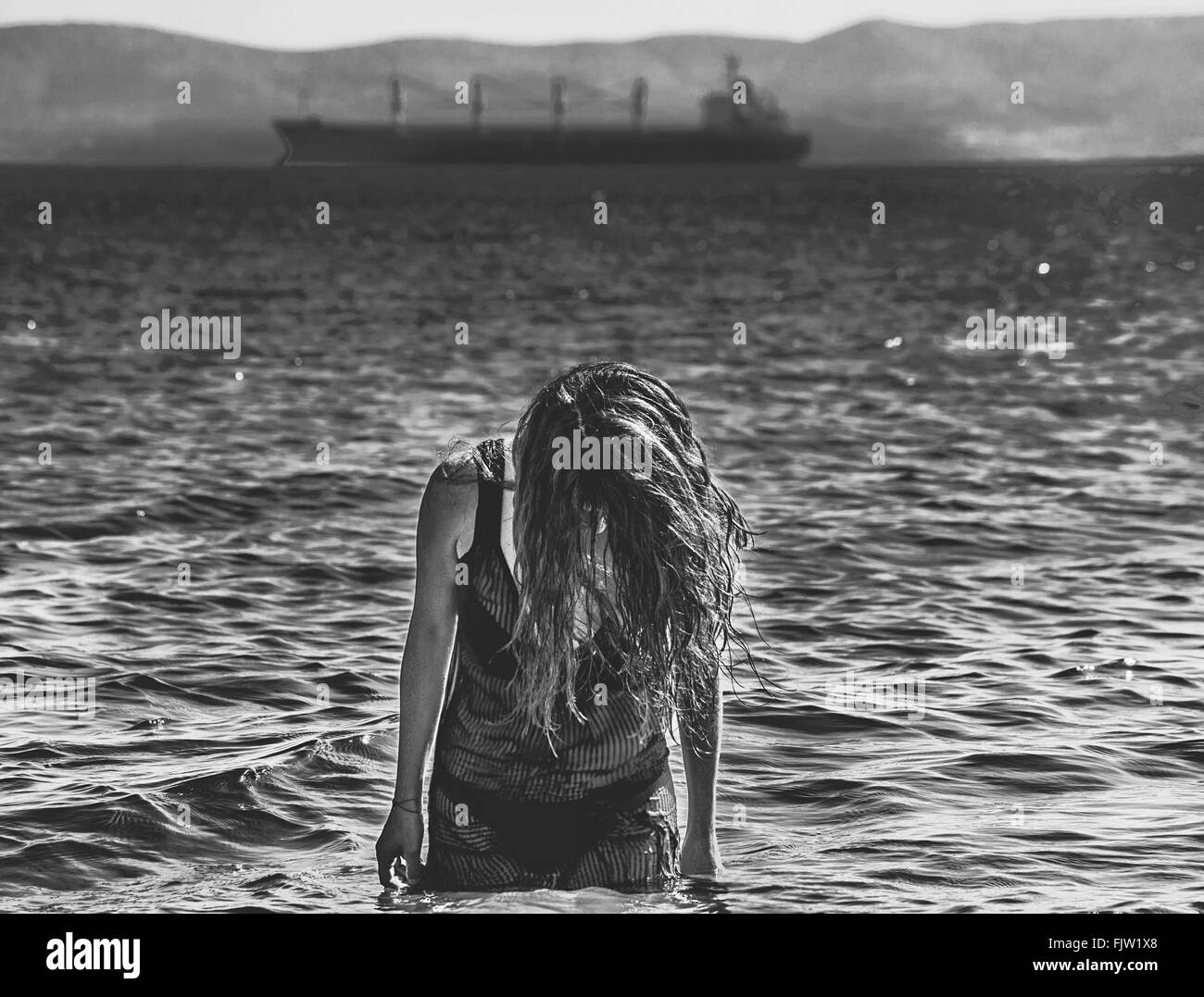 Woman In Bikini Standing In Sea Against Ship - Stock Image