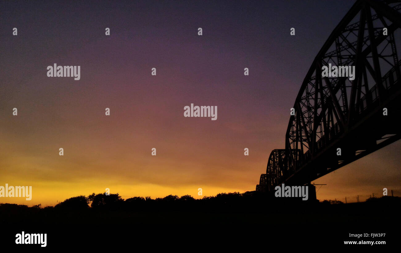 Silhouette Cantilever Bridge Against Sunset Sky - Stock Image