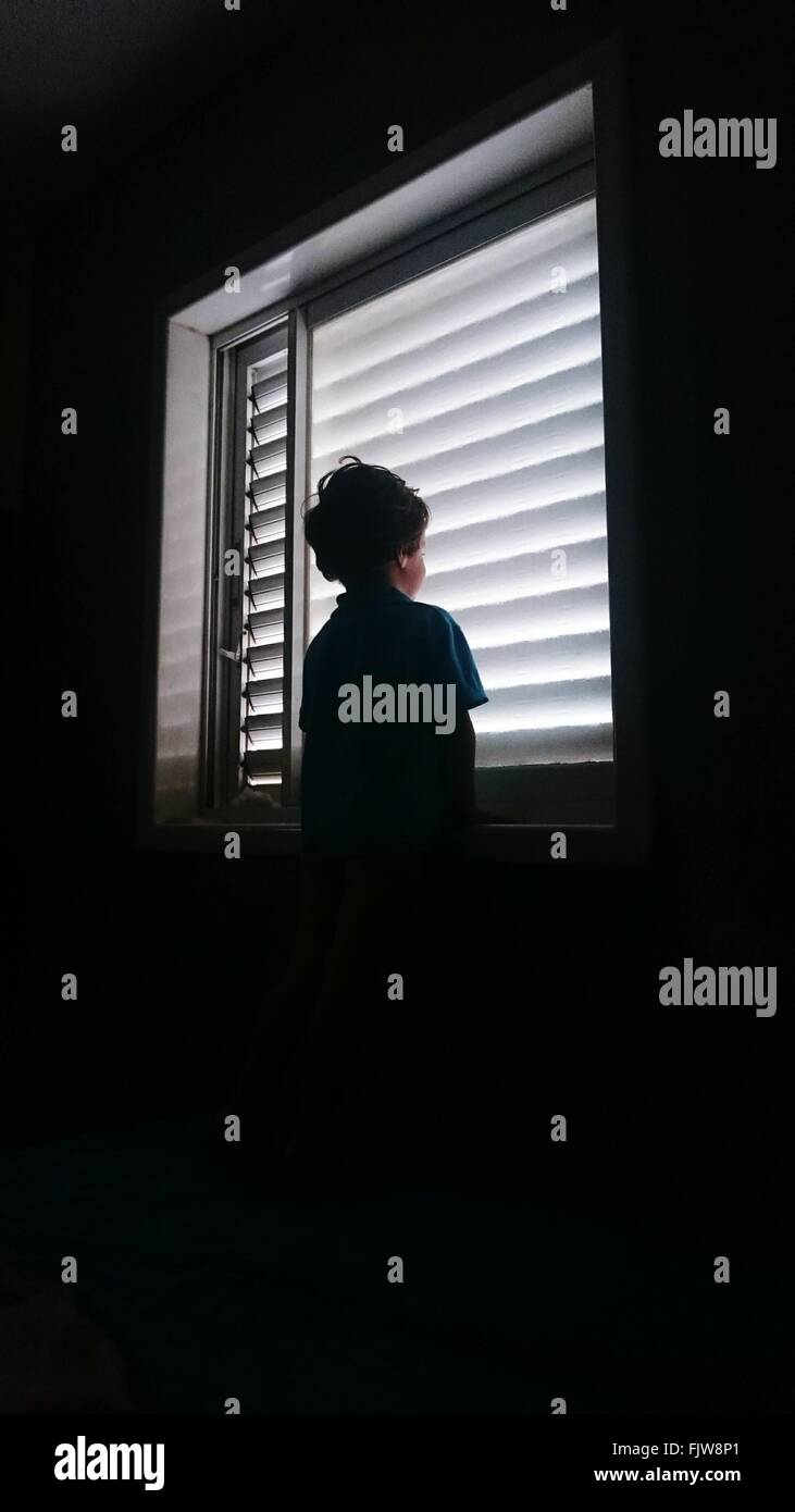 Low Angle View Of Boy Standing Against Window - Stock Image