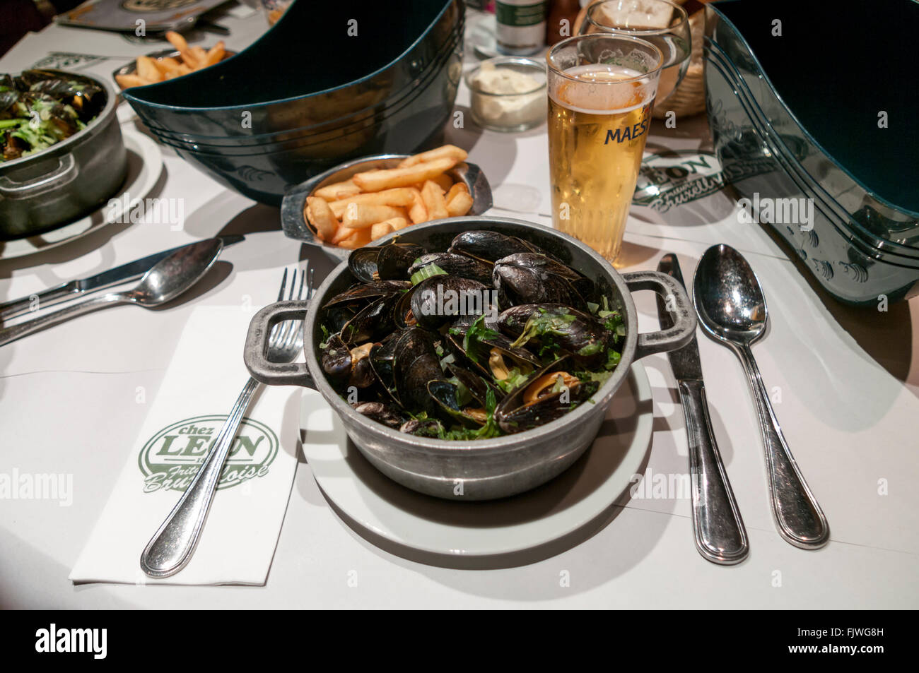 Moules marinières et frites; mussels with fries, served at Chez Léon restaurant in Brussels, Belgium. - Stock Image