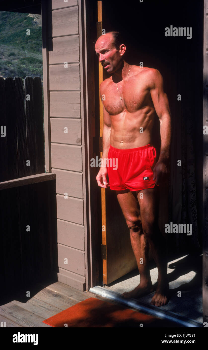 Photographer Chad Ehlers in 40s wearing swimming trunks standing outside door of apartment in Laguna Beach, California - Stock Image