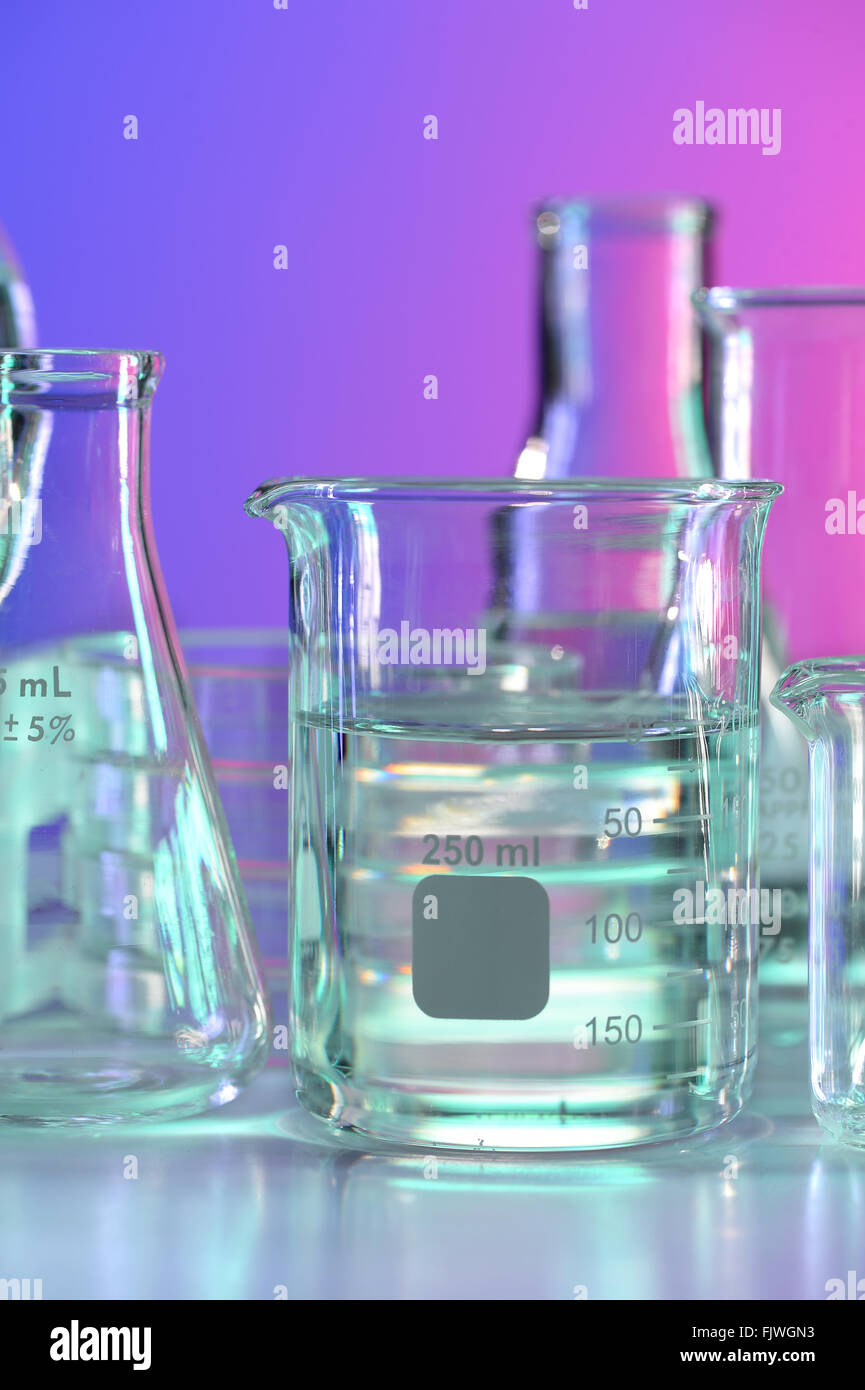 Beaker with clear fluid on laboratory table Stock Photo