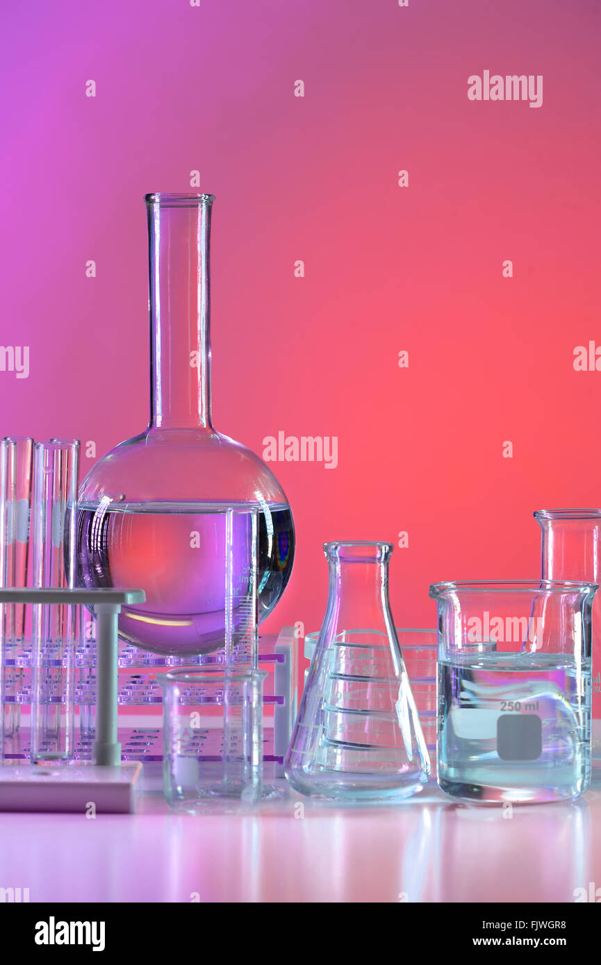 Laboratory glassware over colored background - Stock Image
