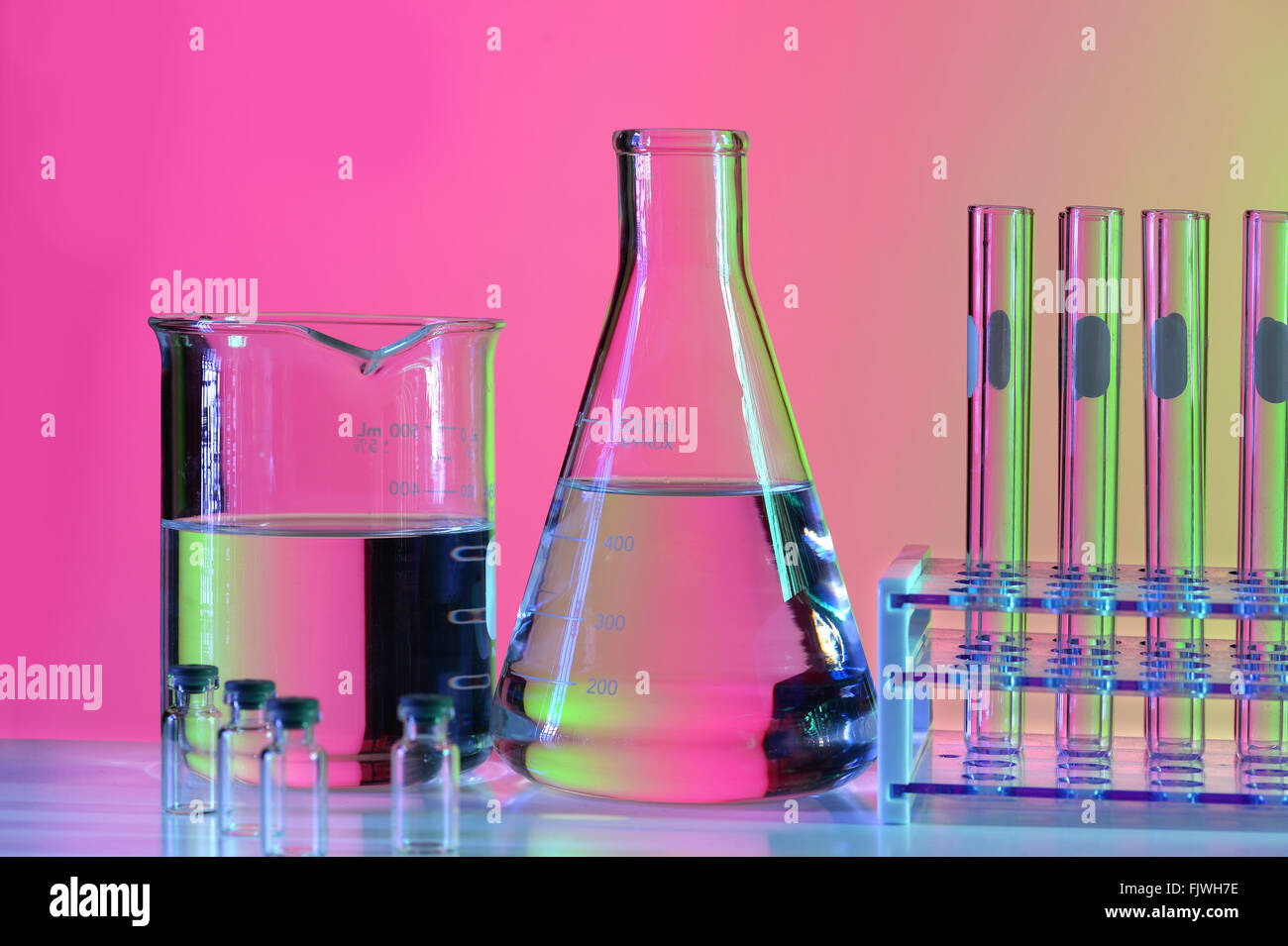 Laboratory glassware on reflective table over colorful background - Stock Image