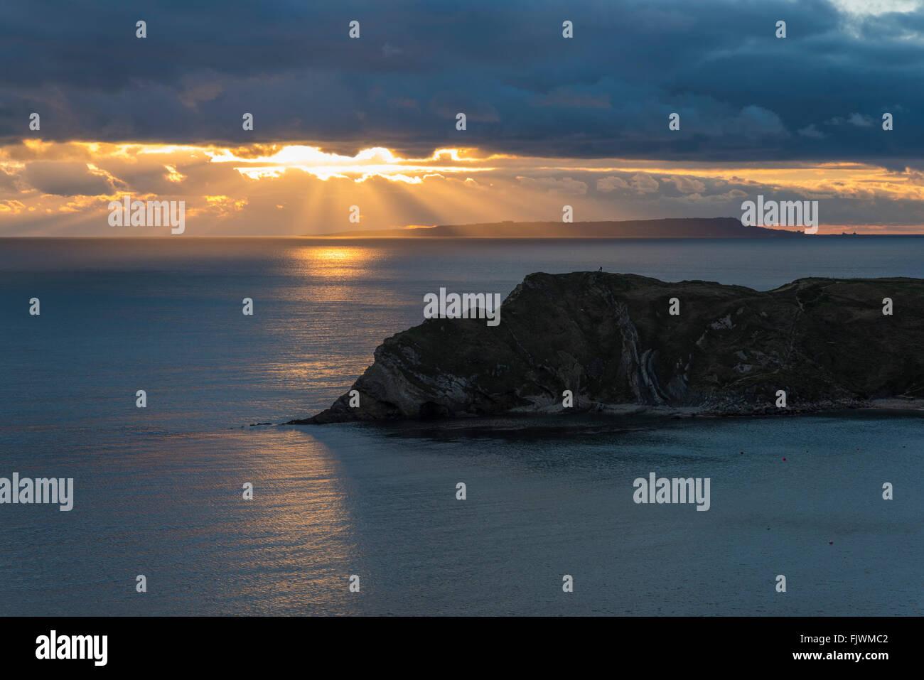 Sun beams shining through the cloud viewed from Lulworth Cove on Dorset's Jurassic Coast, UK - Stock Image