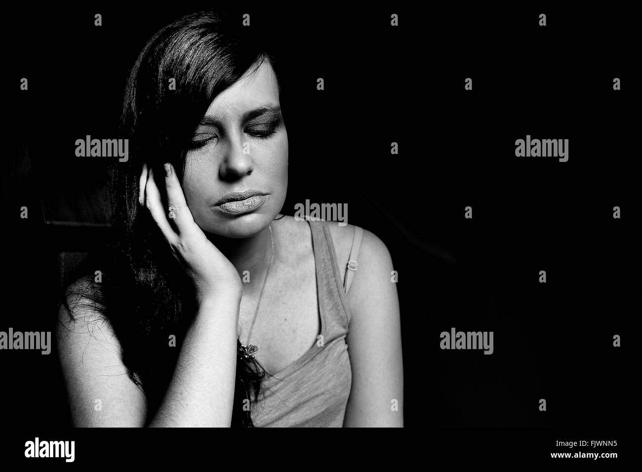 Young Woman With Eyes Closed Against Black Background - Stock Image