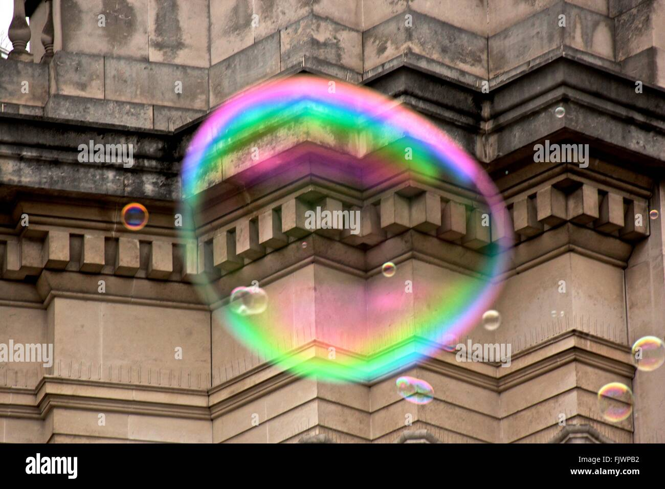 Low Angle View Of Colorful Soap Bubbles Against Old Building - Stock Image
