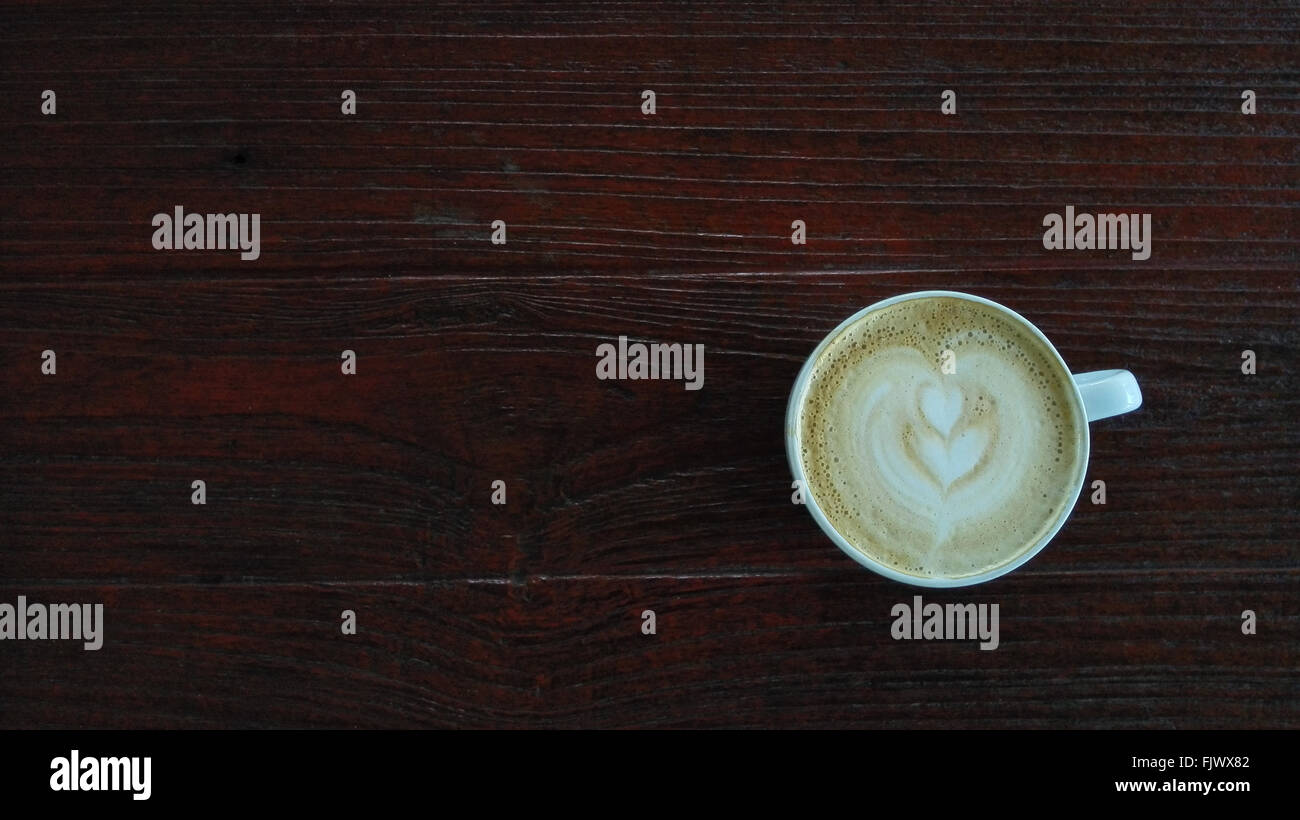 Coffee cup top view on wooden table background - Stock Image
